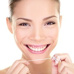 Smiling woman holding dental floss