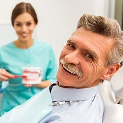 An older gentleman smiling while seated in the dentist's chair and a hygienist shows him how to properly care for his dentures