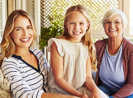 Mother, daughter, and granddaughter smiling together