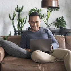 person with full dentures smiling while using laptop