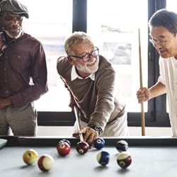 friends playing pool together after denture placement