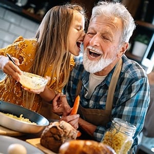 An older man cooks with his granddaughter and shows off his healthier, longer-lasting smile