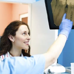 A patient looking at an X-ray with a dentist.