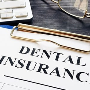 Dental insurance on clipboard for cost of dental implants in Fairfax