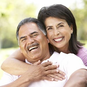 Smiling couple with dental implants in Fairfax