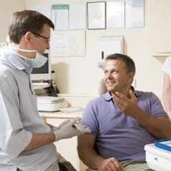 A dentist having a discussion with a male patient