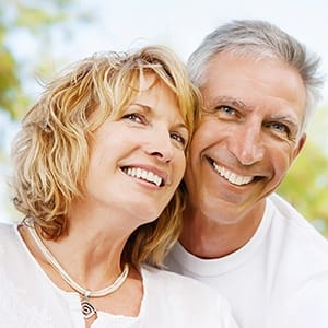 Smiling man and woman outdoors after metal free dental restoration