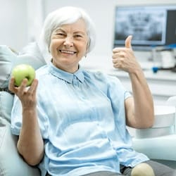 An older woman holding an apple and giving a thumbs up after receiving her dental implants