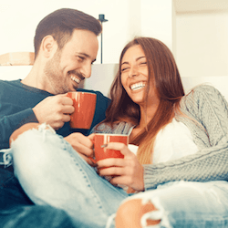Couple drinking coffee on sofa after porcelain veneer treatment