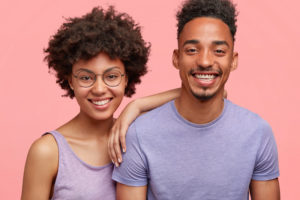 attractive couple smiling against pink background